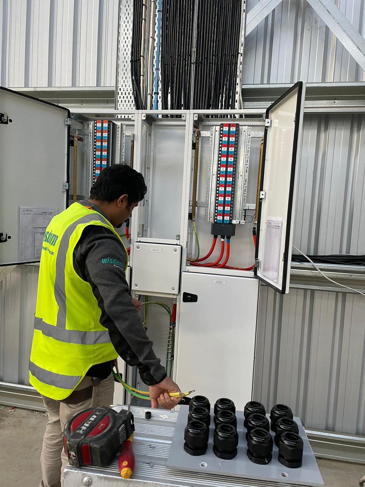 Electricians examining a circuit breaker panel